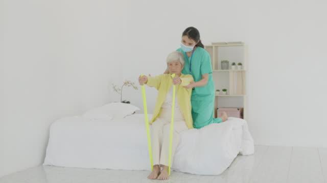 asiatische seniorin mit arthritis im arm erhält arthritis physiotherapie toning band reha durch professionelle krankenschwester oder haus gesundheitshilfe im schlafzimmer zu hause. - hausbesuch stock-videos und b-roll-filmmaterial