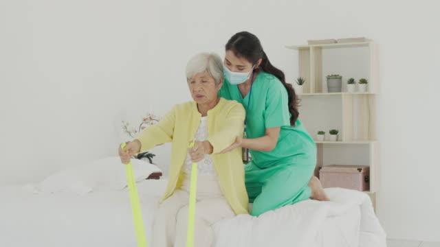 asiatische seniorin mit arthritis im arm erhält arthritis physiotherapie toning band reha durch professionelle krankenschwester oder haus gesundheitshilfe im schlafzimmer zu hause. - ordnung stock-videos und b-roll-filmmaterial