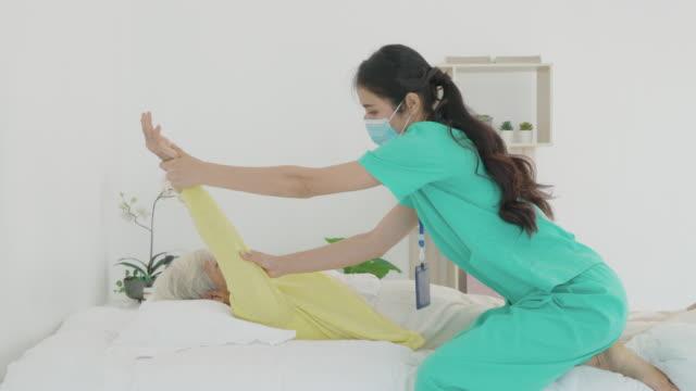 asiatische seniorin mit arthritis in der schulter erhält arthritis physiotherapie reha von professionellen krankenschwester oder haus gesundheitshilfe im schlafzimmer zu hause. - hausbesuch stock-videos und b-roll-filmmaterial