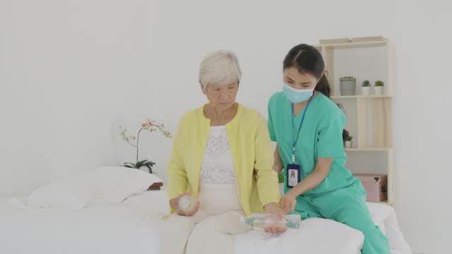 asiatische seniorin mit arthritis in ihrem handgelenk erhält arthritis physikalische therapie wasserflasche hantel reha von professionellen krankenschwester oder haus gesundheitshelfer im schlafzimmer zu hause. - hausbesuch stock-videos und b-roll-filmmaterial