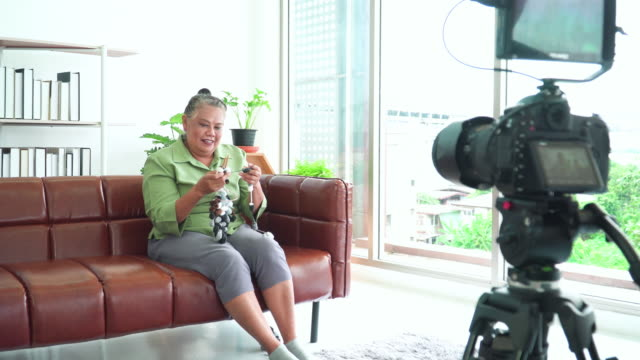 カジュアルな服を着たアジアの先輩女性、インフルエンサー、youtuberはソファに座ってブログを書き、説明し、モニターでデジタル一眼レフカメラにかぎ針編みを編む方法を示しています。� - キャンペーンバッジ点の映像素材/bロール