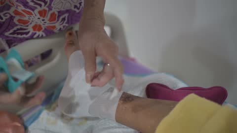 asian senior woman wrapping her bedridden husband legs due to diabetes and pressure-sore injury - husband stock videos & royalty-free footage