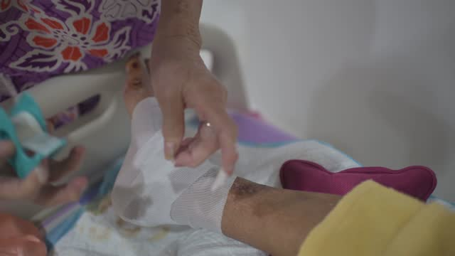 asian senior woman wrapping her bedridden husband legs due to diabetes and pressure-sore injury - wounded stock videos & royalty-free footage