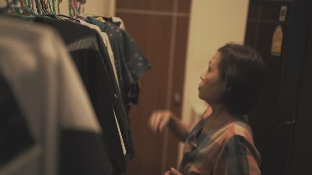 stockvideo's en b-roll-footage met aziatische hogere vrouwen schikken kleren. - alleen één oudere vrouw