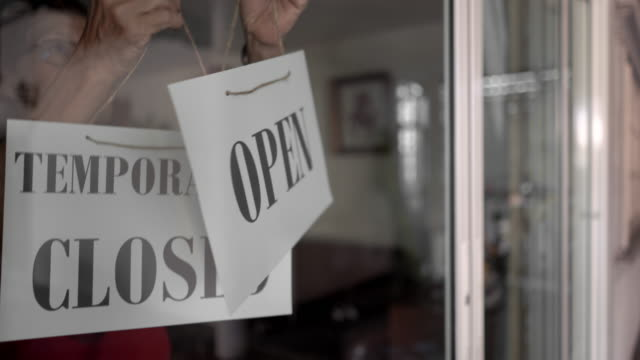 asian senior women changing open to temporarity closed sign on shop door - closed sign stock videos & royalty-free footage