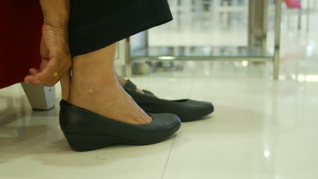 Asian senior women fitting new shoe at store