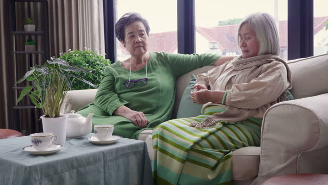 asian senior women friends enjoying afternoon tea while setting on sofa in living room, relaxing and spending time together at home - cup stock videos & royalty-free footage