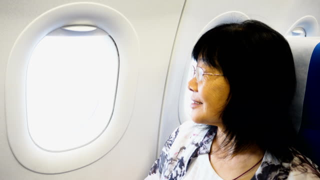 Asian senior women looking out of plane window