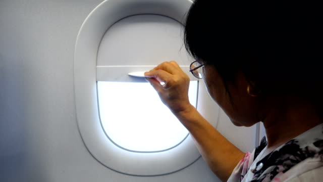 asian senior women looking out of plane window - windows stock videos and b-roll footage