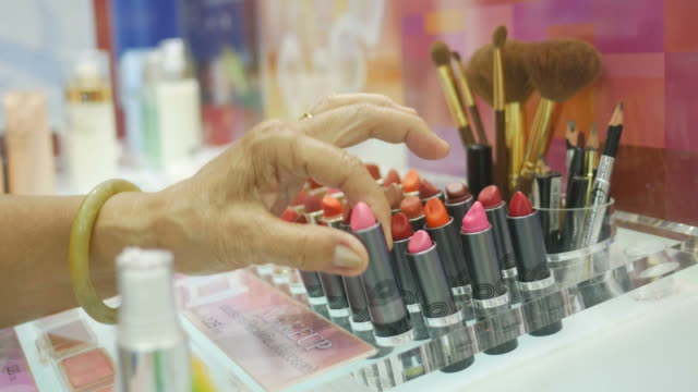 Asian senior women testing lipstick at store