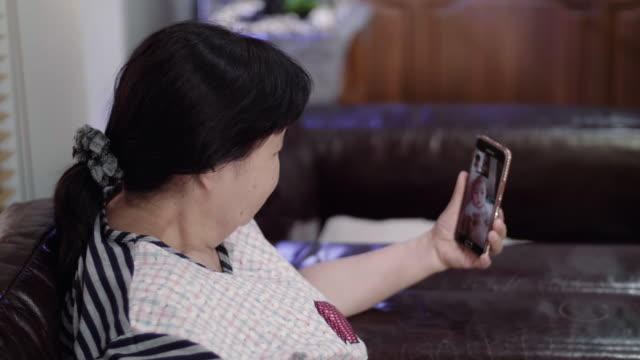 Asian Senior Women Using A Smart Phone At Living Room