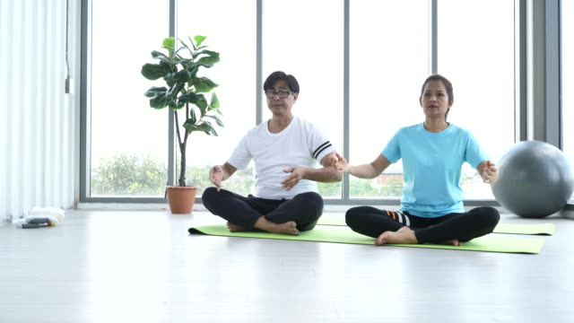 asian senior yoga home fitness - zen like stock videos & royalty-free footage