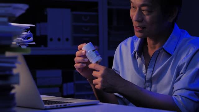 vidéos et rushes de les personnes âgées asiatiques âgées de 57 ans qui parlent à un travailleur de la santé par vidéoconférence à la maison pendant la distanciation sociale à l'aide d'un ordinateur labtop et d'une technologie de vidéoconférence la nuit où e - new age concept