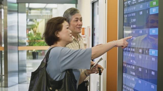 アジアの高齢者が到着出発ボードの時間を確認 - passenger点の映像素材/bロール