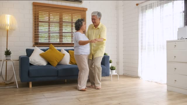asian seniors couple enjoy dancing  in living room at home.aging at home concept - sofa stock videos & royalty-free footage