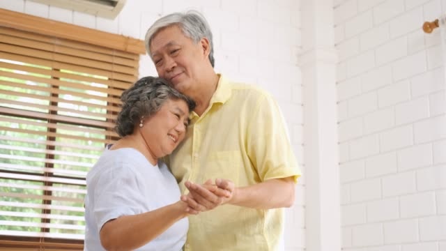 asian seniors couple enjoy dancing in living room at home.aging at home concept. - slow dancing stock videos and b-roll footage
