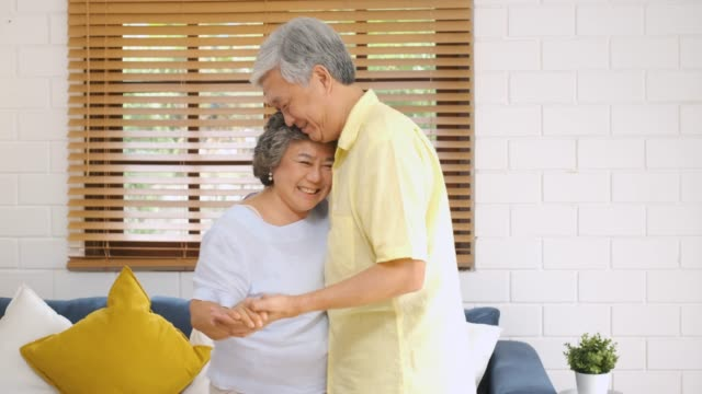 asian seniors couple enjoy slow dancing in living room at home.aging at home concept. - slow dancing stock videos and b-roll footage