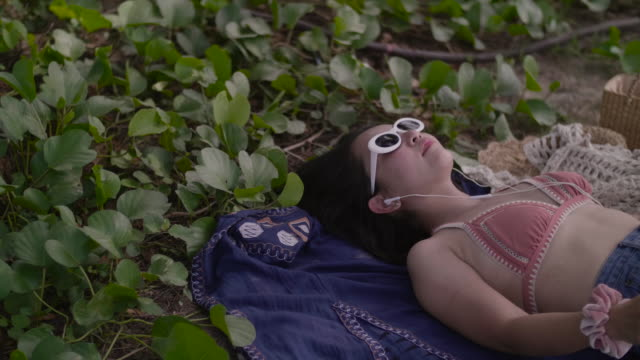 asian sexy girl in bikini lying on the beach enjoying inserting earphones. - nodding head to music stock videos & royalty-free footage