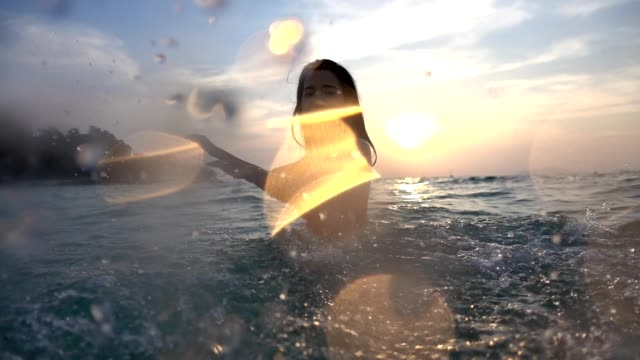 Asian sexy girl in bikini with wet hair and lips Having Fun Splashing in the sunset at sea