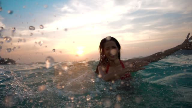 vídeos de stock e filmes b-roll de asian sexy girl in bikini with wet hair and lips having fun splashing in the sunset at sea - par
