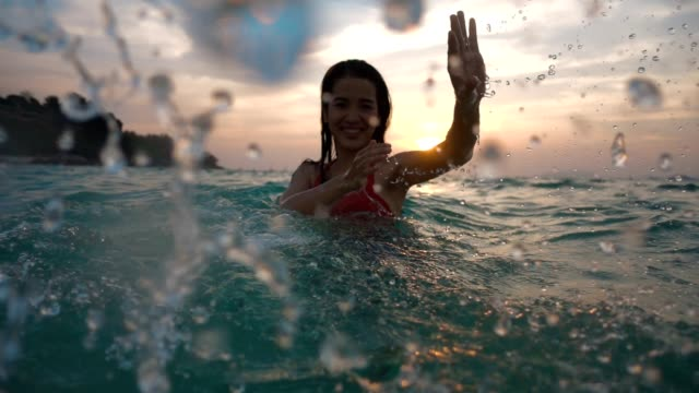 stockvideo's en b-roll-footage met aziatische sexy meisje in bikini met natte haren en lips having fun spatten in de zonsondergang op zee - verblijfsoord