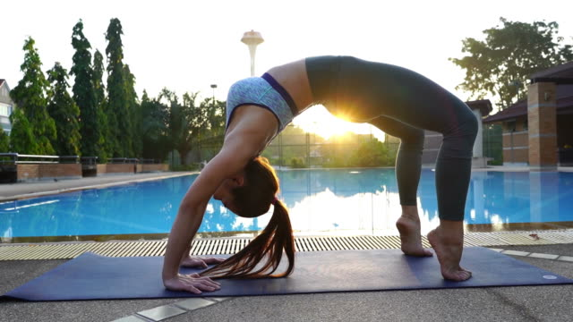 asian sexy woman workout yoga and pilates at poolside, sun flare - deltoid stock videos and b-roll footage