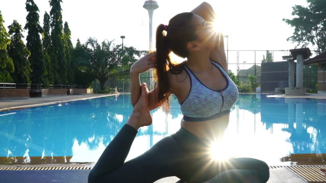 asian sexy woman workout yoga and pilates at poolside, sun flare  , zoom out - deltoid stock videos and b-roll footage