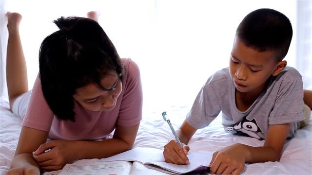 Asiatische Geschwister zu Hause Hausaufgaben