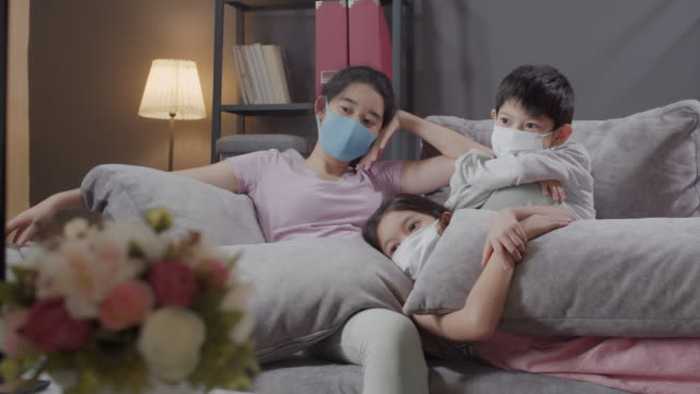 asian sibling enjoy watching a television in the living room at home with coronavirus 0r covid-19 quarantine situation. reduce germ spread concepts. brother and sister happiness while watching tv at home. - sibling stock videos & royalty-free footage