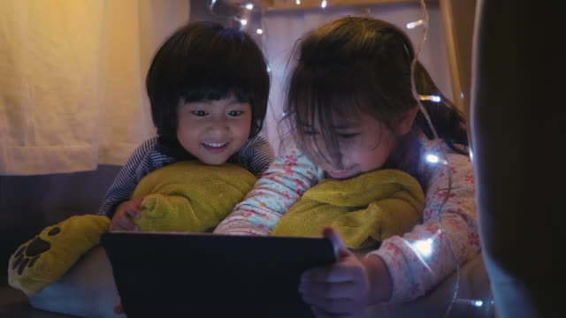 asian sibling have fun in camping tent at home while watching digital tablet in the living room at home. - sister stock videos & royalty-free footage