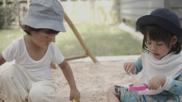 asian sibling playing with toys in sandbox at home. - 2 kid in a sandbox stock videos and b-roll footage
