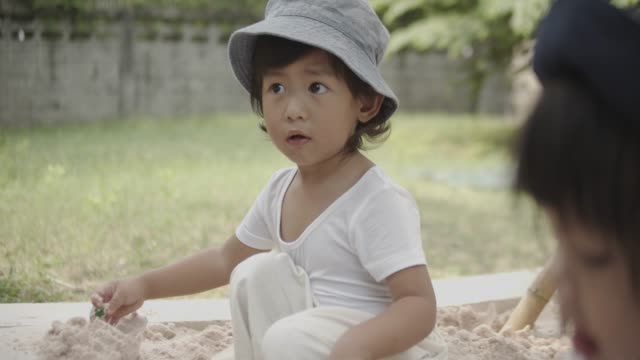 asian sibling playing with toys in sandbox at home. - digging stock videos and b-roll footage