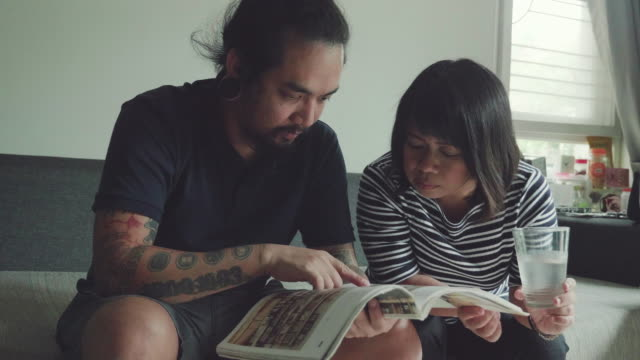 asian sibling reading a book together on sofa - magazine stock videos & royalty-free footage