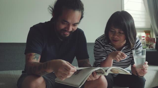 vídeos de stock, filmes e b-roll de irmãos asiáticos, ler um livro juntos no sofá - irmão