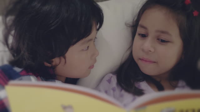 asian sibling reading story book at night. - storytelling stock videos & royalty-free footage