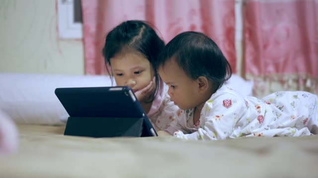 asian siblings watching and playing tablet - sibling stock videos & royalty-free footage
