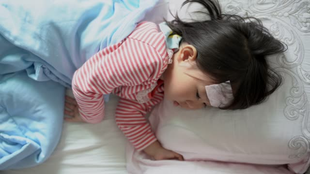 asian sick little girl lying in bed with a high fever - 黄色ブドウ球菌点の映像素材/bロール