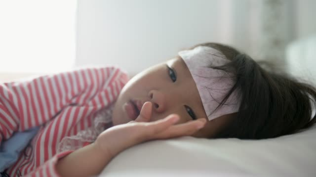 asian sick little girl lying in bed with a high fever - fieber stock-videos und b-roll-filmmaterial