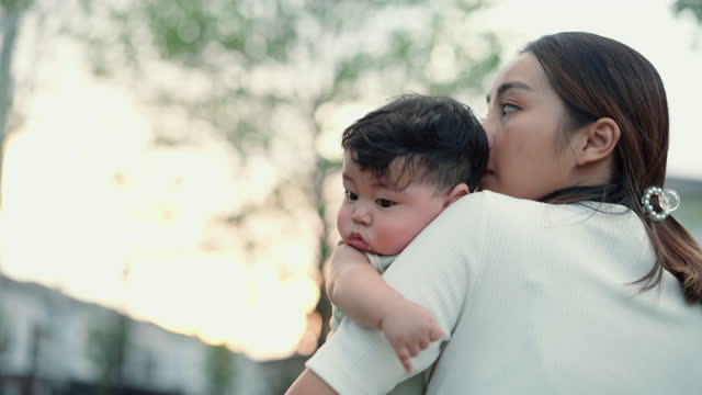 asiatiska ensamstående mamma vagga hennes barn att sova på parken - bära bildbanksvideor och videomaterial från bakom kulisserna