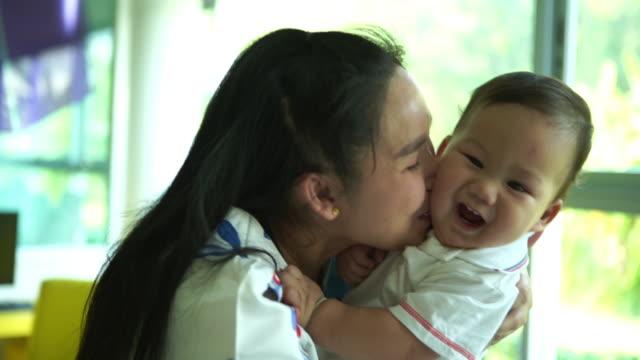 vídeos de stock e filmes b-roll de asian single mom playing and kissing with her baby boy - cuidar de crianças