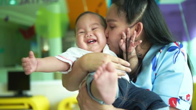 asiatische alleinerziehende mutter spielt und küsst mit ihrem kleinen jungen - darstellen stock-videos und b-roll-filmmaterial