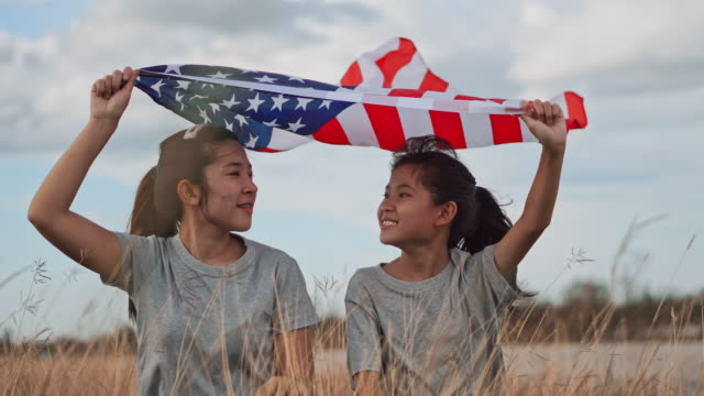 asian sisters happy and fun with american flag usa celebrate 4th of july - circa 4th century stock videos & royalty-free footage
