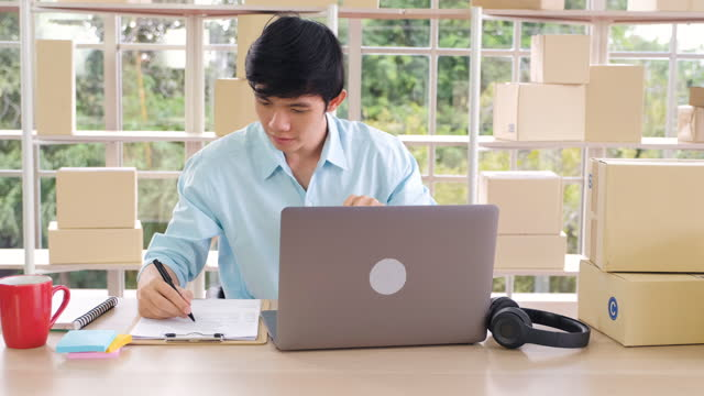 asian small business owner writing order from customer to delivery at home with stock checking on laptop.online small business e-commerce concept - examining stock videos & royalty-free footage