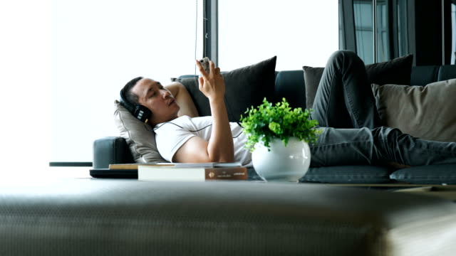 Asian smart man is lying down at sofa while listening music in smart phone after work