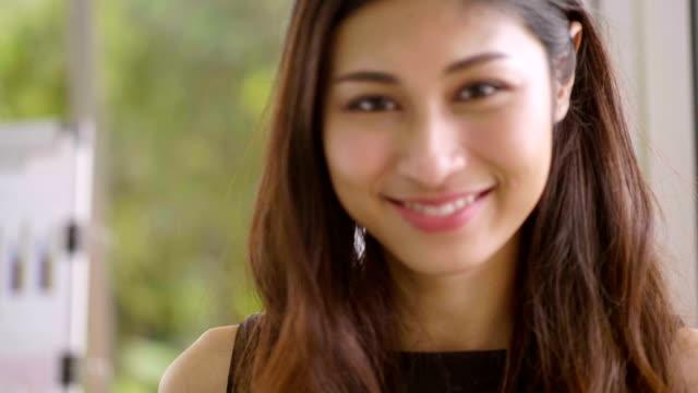 vidéos et rushes de agent intelligent asiatique femme souriante - génération du millénaire