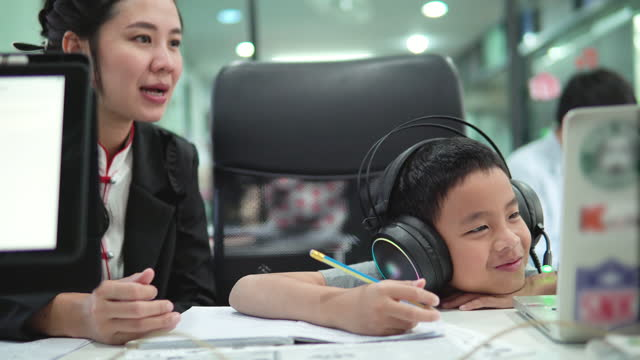asian son attending to online class from home with mother. - attending stock videos & royalty-free footage