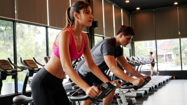 asian sport man heat up cardio on station bike at gym.healthy,city life style concept. - loss stock videos & royalty-free footage