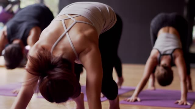 asian sport woman and caucasian white training yoga in yoga studio coaching by trainer,open light from nature.healthy,city life style concept.slow motion footage. - studio camera video stock e b–roll