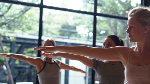 vídeos de stock, filmes e b-roll de mulher asiática do esporte e ioga branca caucasiano do treinamento no estúdio da ioga que treina pelo instrutor, luz aberta da natureza. saudável, conceito do estilo de vida da cidade. filmagem em câmara lenta. - equilíbrio