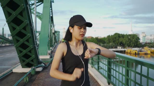 スマートウォッチから心拍数をチェックするアジアのスポーツ女性 - 女子トラック競技点の映像素材/bロール
